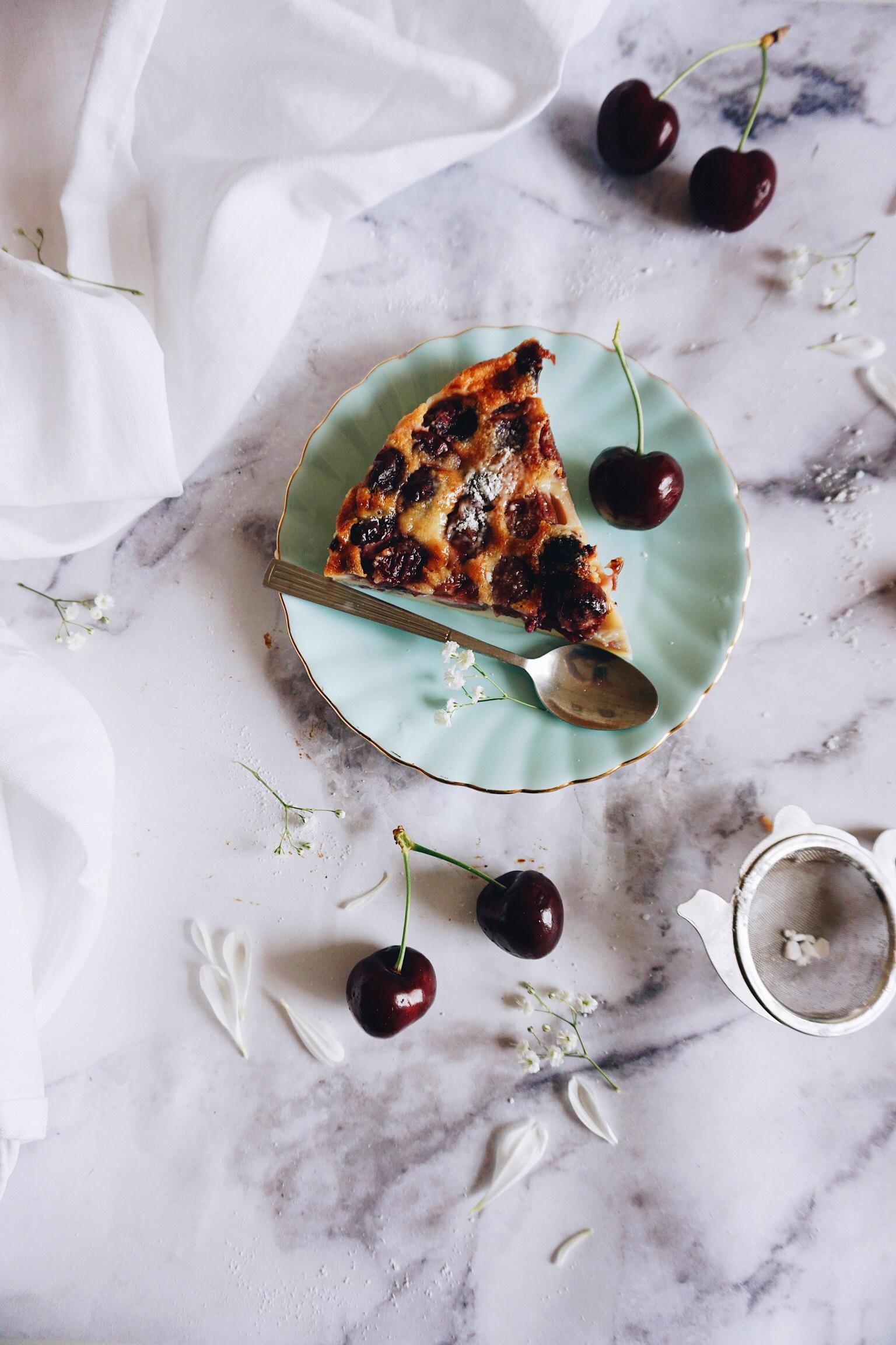 wedge of French cherry custard dessert known as clafoutis served with fresh dark red summer cherries