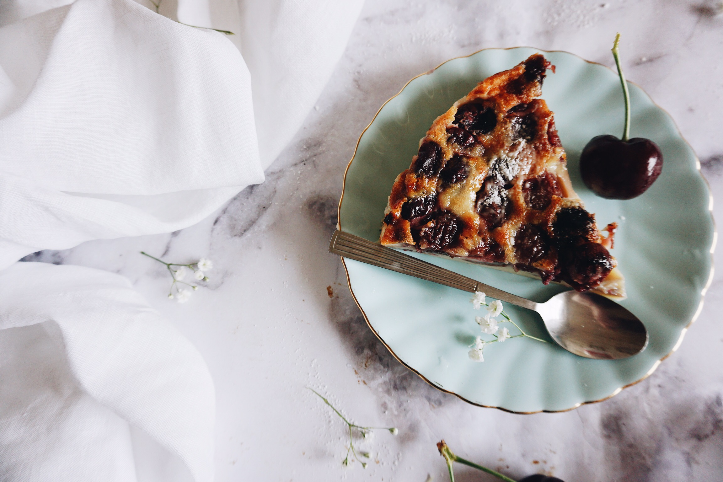 Cherry clafoutis on pale green flower plate next to linen table cloth on marble counter sprinkled icing sugar
