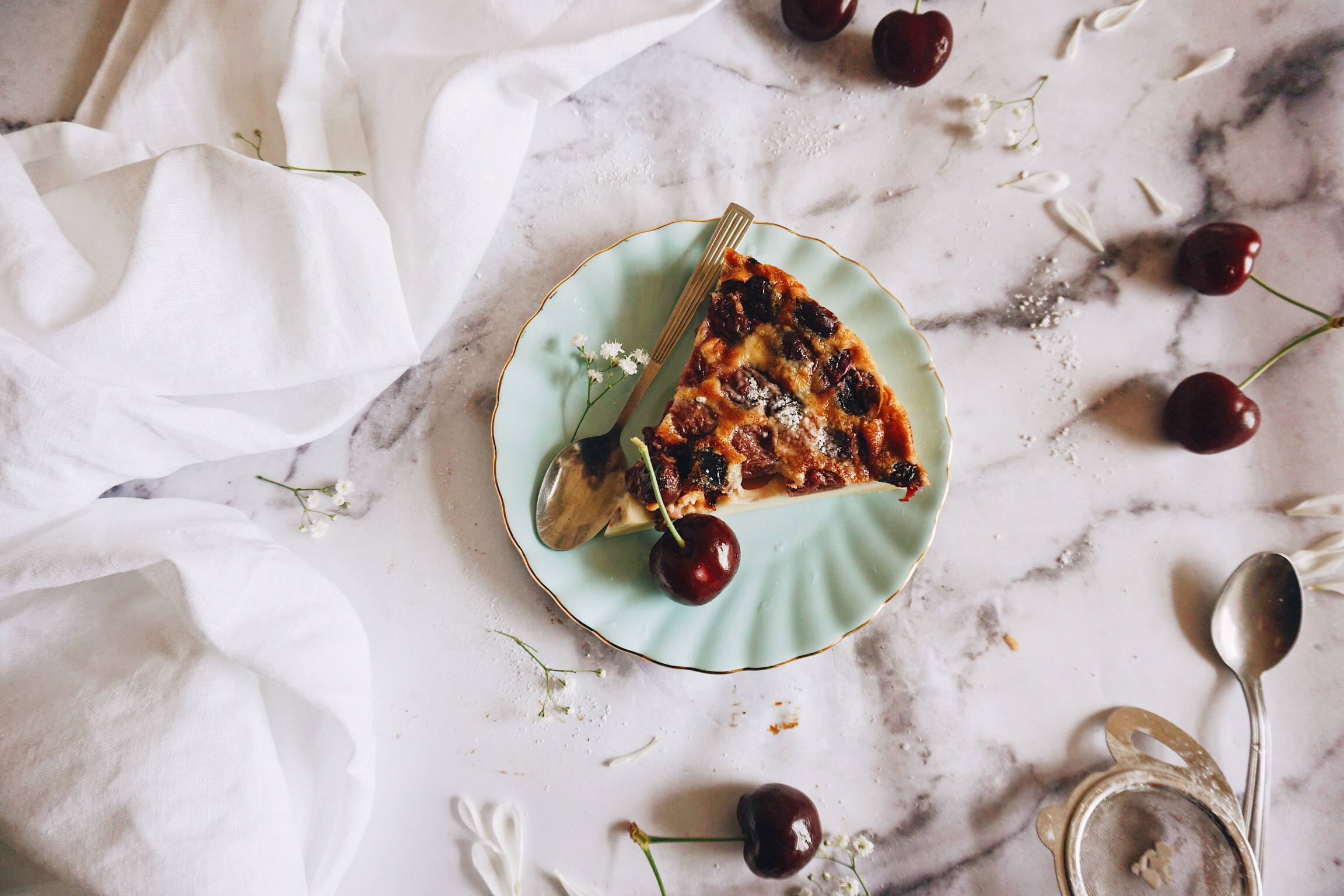 Wedge of French cherry flan tart known as clafoutis surrounded by cherries flowers dusted with icing sugar