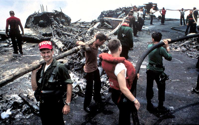 Grimy and exhausted, crewmen of USS Forrestal and her airwing continue firefighting efforts in the aftermath of the blaze that killed 134 of their shipmates 29 July 1967. The ship was on station off the coast of Vietnam. In the background are what remains of a row of F-4B Phantoms that were parked along the starboard stern quarter. (Navy released image.)