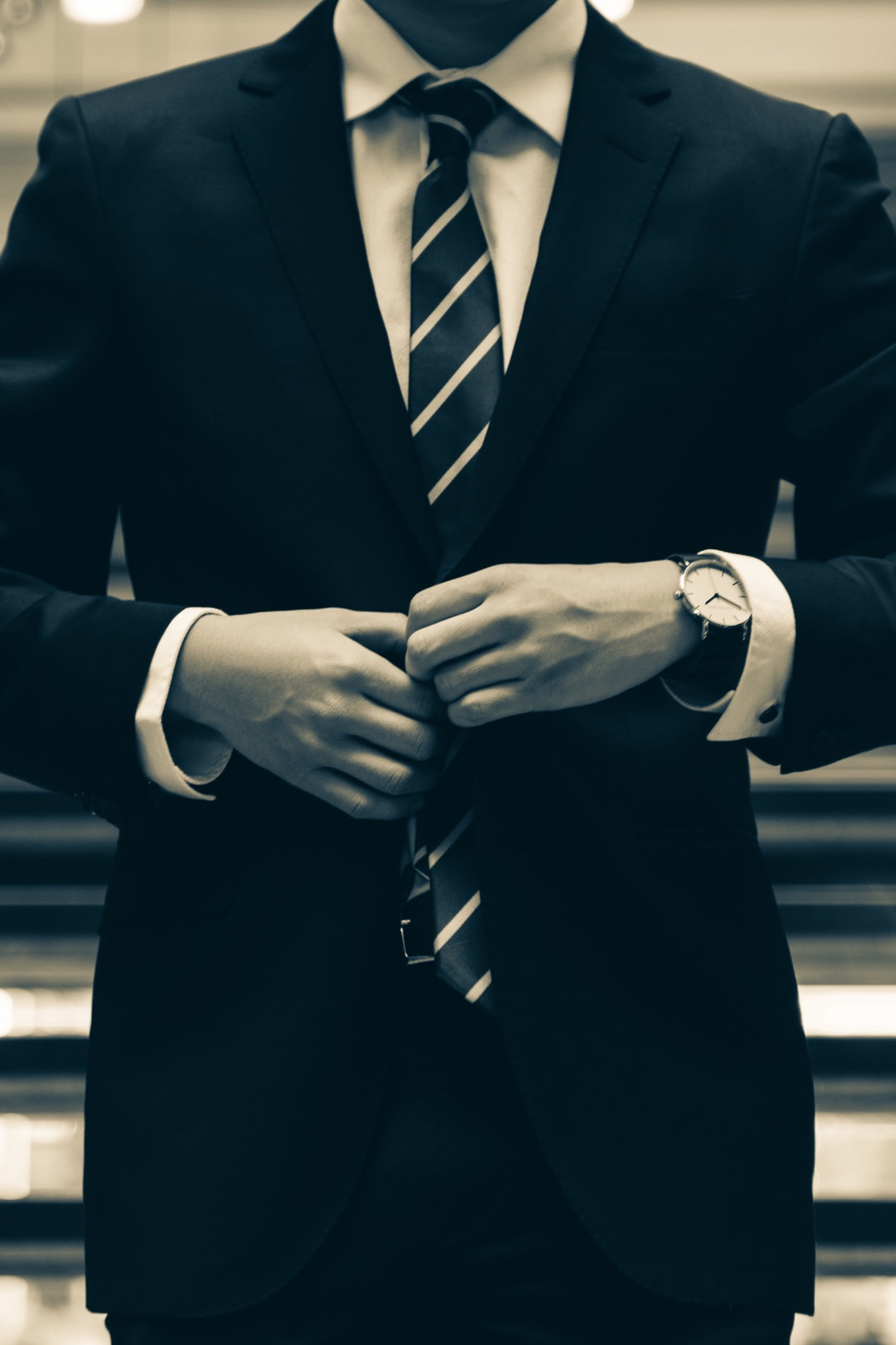 Man in a corporate setting buttoning his suit