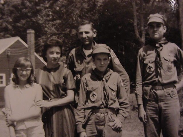 Bill Ray (the Scout Master) and his wife Margaret and daughter Cathy, and Forrest Melton and Eddie Melton, standing in front of the Scout lodge.