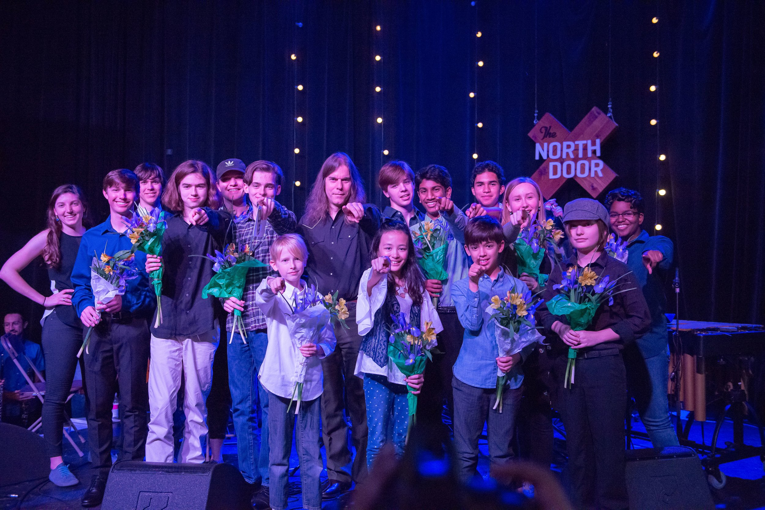 Young composers on stage holding flower bouquets and pointing at the camera.
