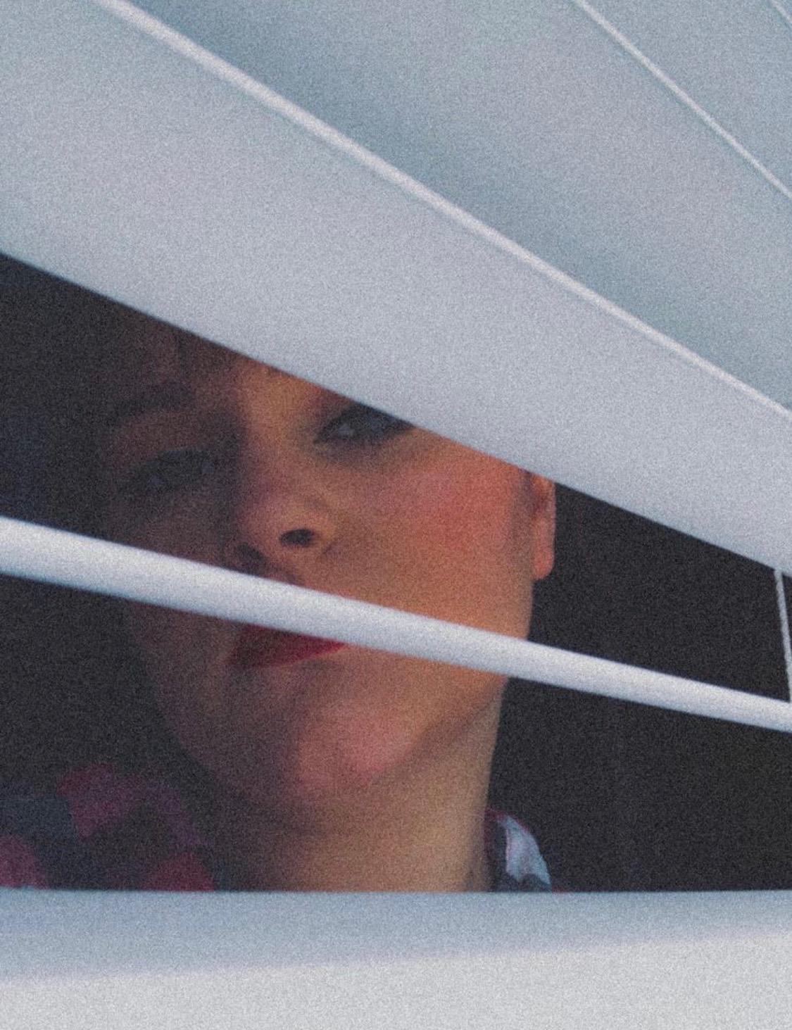 Briggy Jones looking through blinds