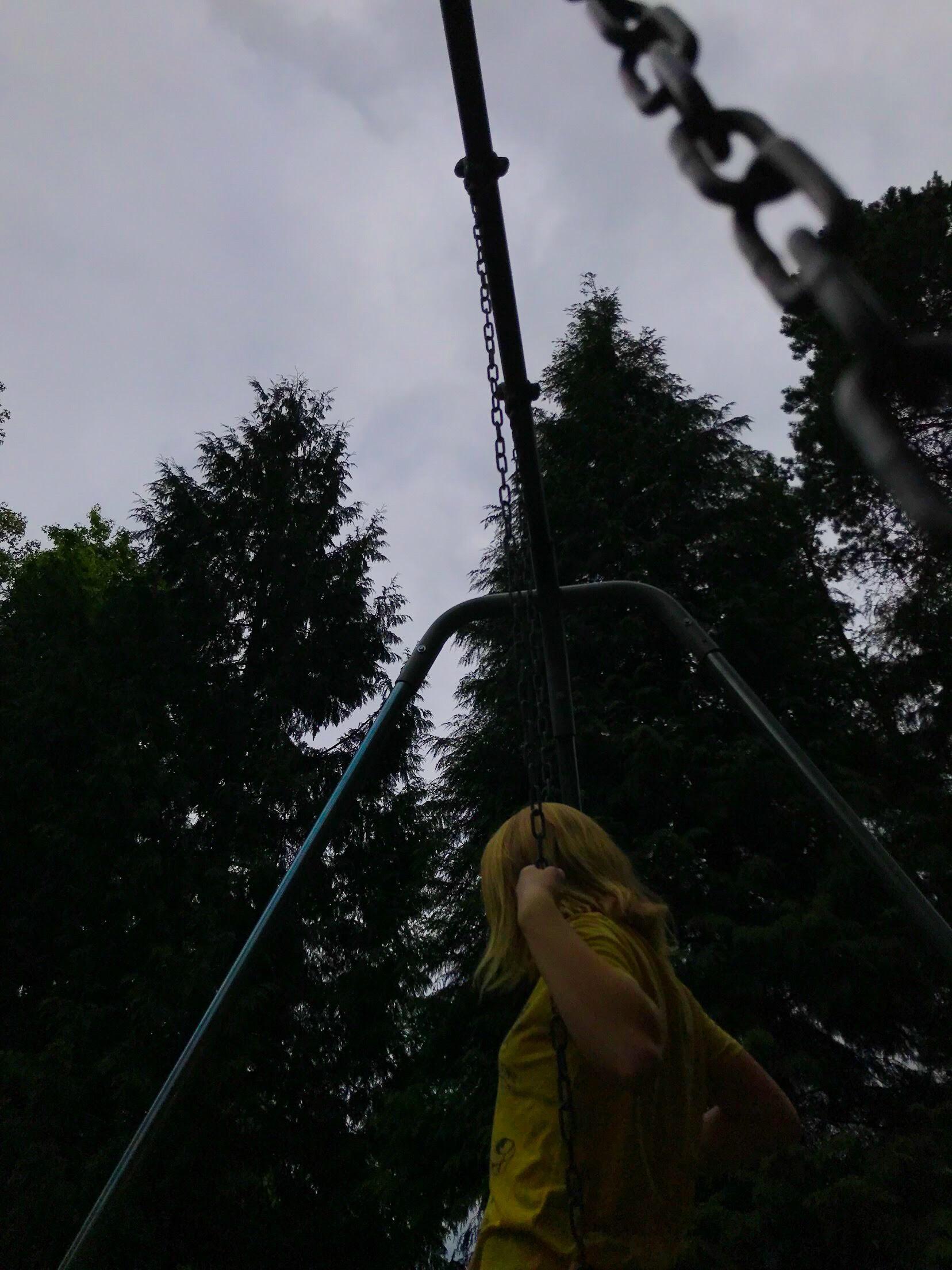 Girl in yellow shirt on swing outside