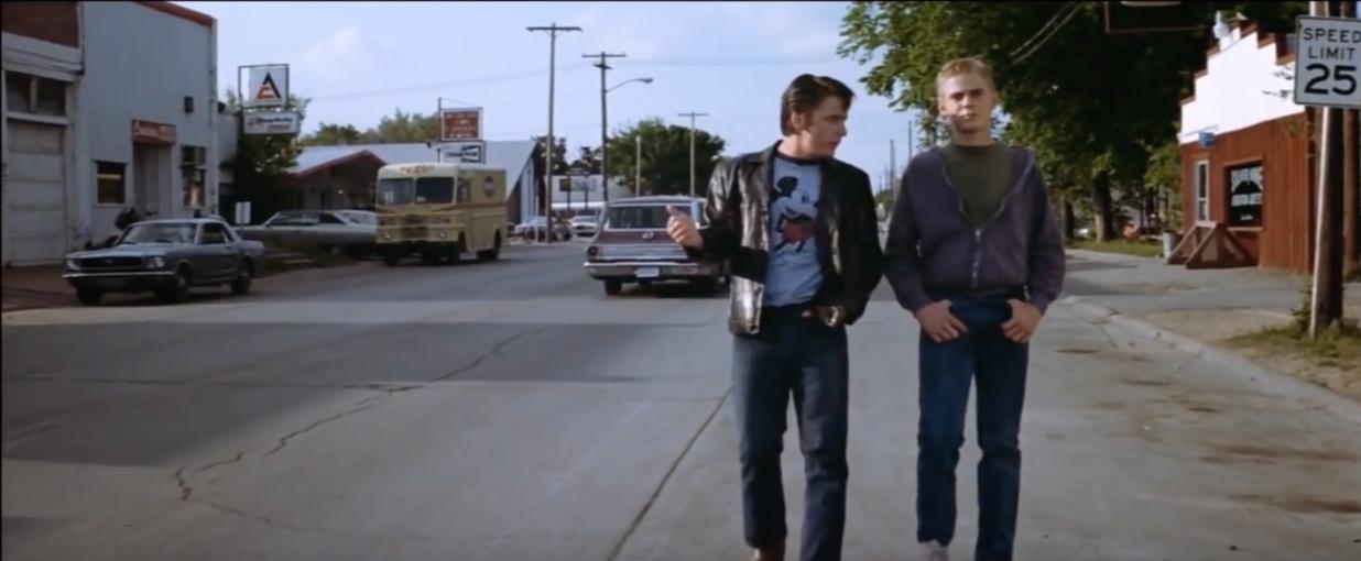Outsiders Two Bit and Ponyboy walking on street