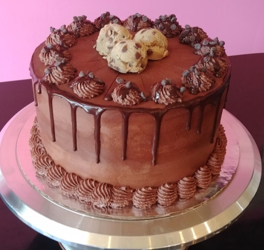 Chocolate Chip Cookie Dough - Vanilla Chocolate Chip Cake, Filled with Chocolate Chip Cookie Dough, Topped with Chocolate Frosting, Ganache & Chocolate Chips.