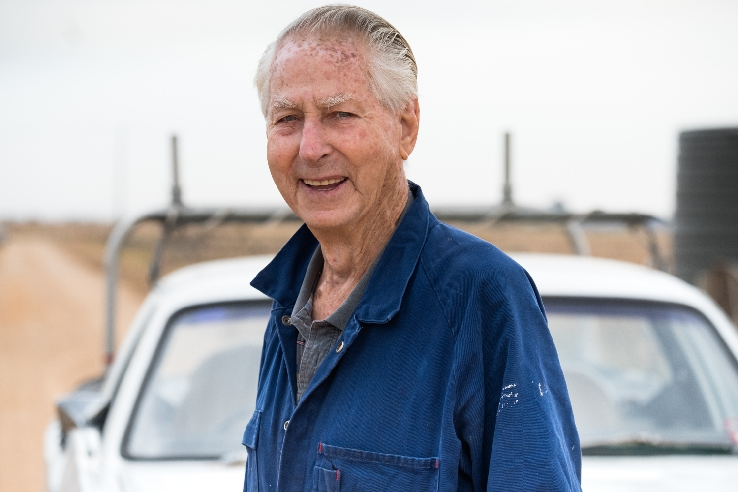 Close up of older man in front of his car in rural area.jpg