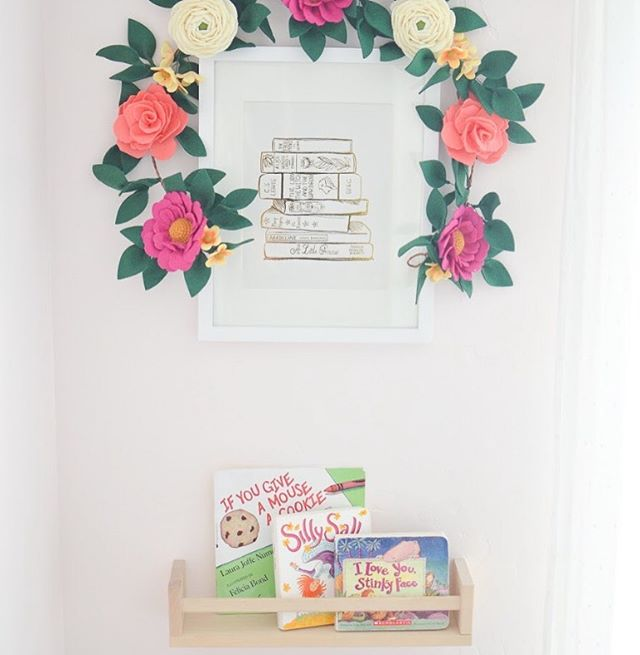 The cutest little reading nook featuring our classic stack of books print in gold foil & topped with a @thegreyrose floral garland. 😍