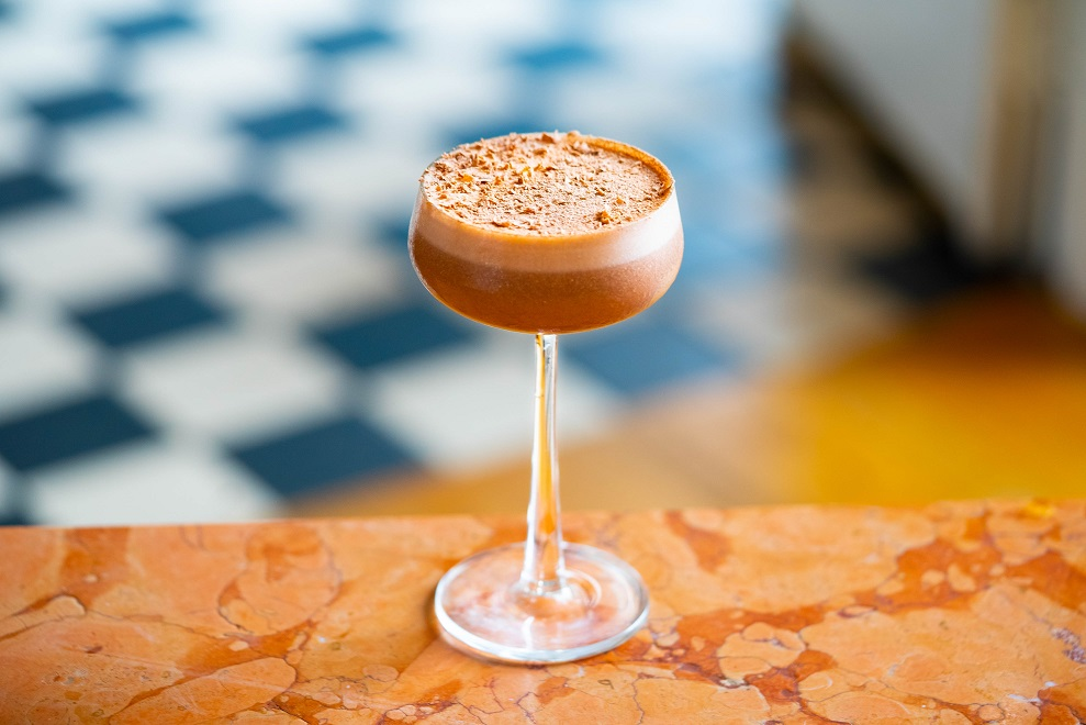 CHOCOLATE ORANGE MARTINI : Tanqueray Gin, Tanqueray Flor de Sevilla Gin, Briottet Crème de Cacao Blanc, Milk, Homemade Orange Peel Syrup and Chocolate, topped with Chocolate Orange Shavings