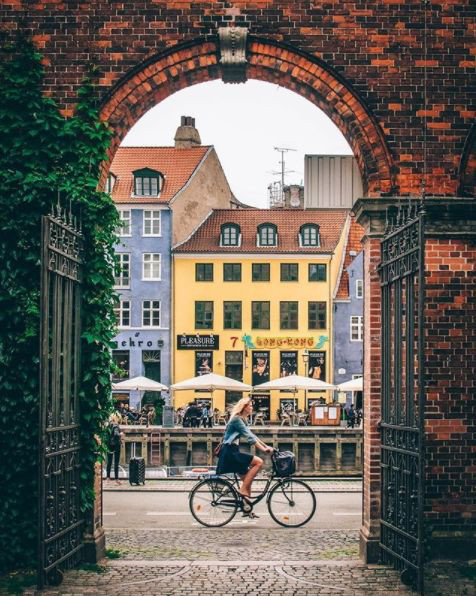 Eco Travel Guide to Copenhagen article. Image of girl on bike cycling through Nyhavn.jpg