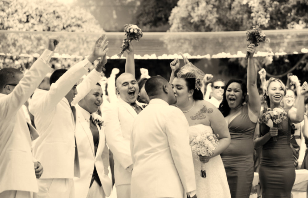 Bride and Groom Kiss After Wedding Ceremony While Wedding Party Cheers