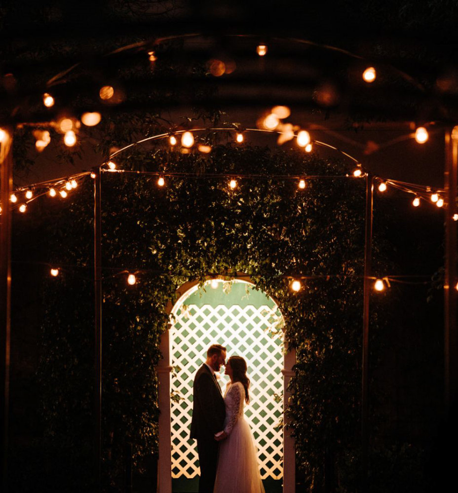 Newly Married Couple Enjoys an Evening Reception Under Outdoor Garden Archway
