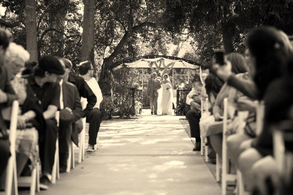 Father walks his daughter down the isle in beautiful outdoor garden ceremony
