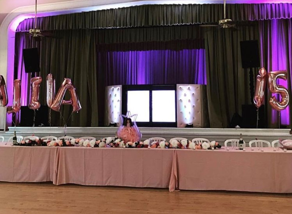 Front stage decorated for pink quinceañera party with banquet tables, balloons, flowers