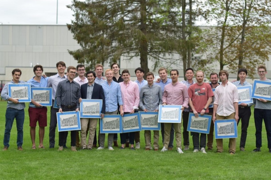 The graduating seniors of the Class of 2019 holding their framed portraits of the chapter house at the New York Zeta Graduation Banquet (May 18, 2019)