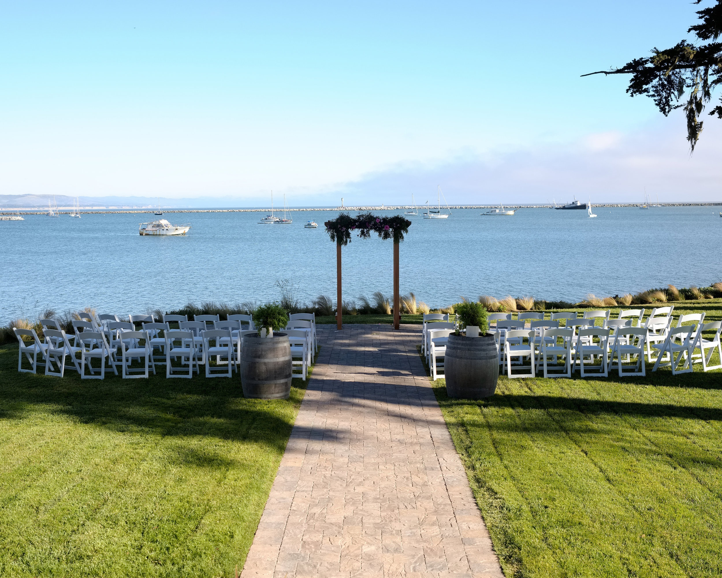 Waterfront Garden - Stunning, private, and unobstructed views of the ocean create the perfect venue for a romantic wedding by the sea. A wide-paved garden path surrounded by grass and a grove of local cypress trees completes the setting.