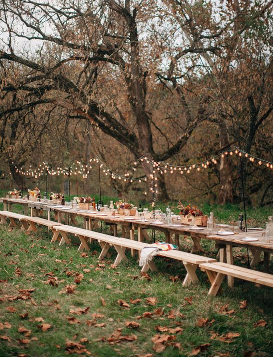 A row of wooden tables, set and decorated with a beautiful rustic theme, matching the fall setting, that includes string lights and flower boxes.