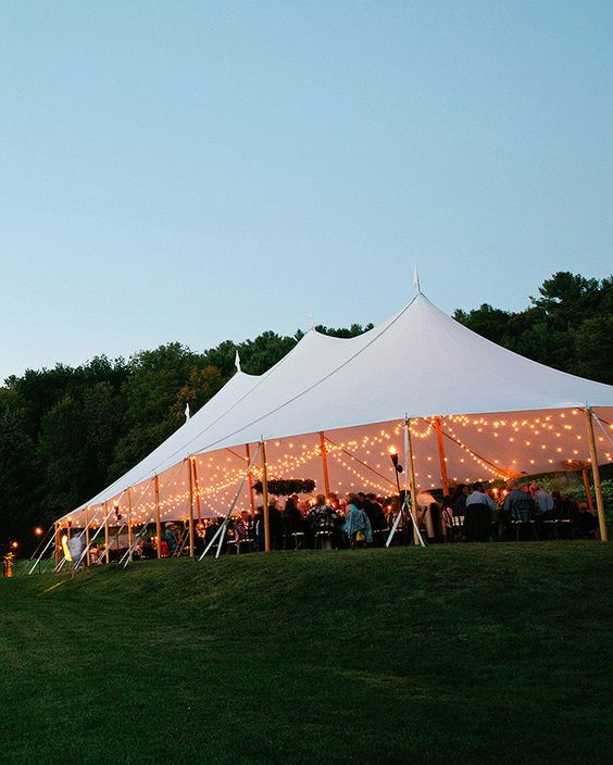 A large white tent with open siding and string lights filled with people at dusk.