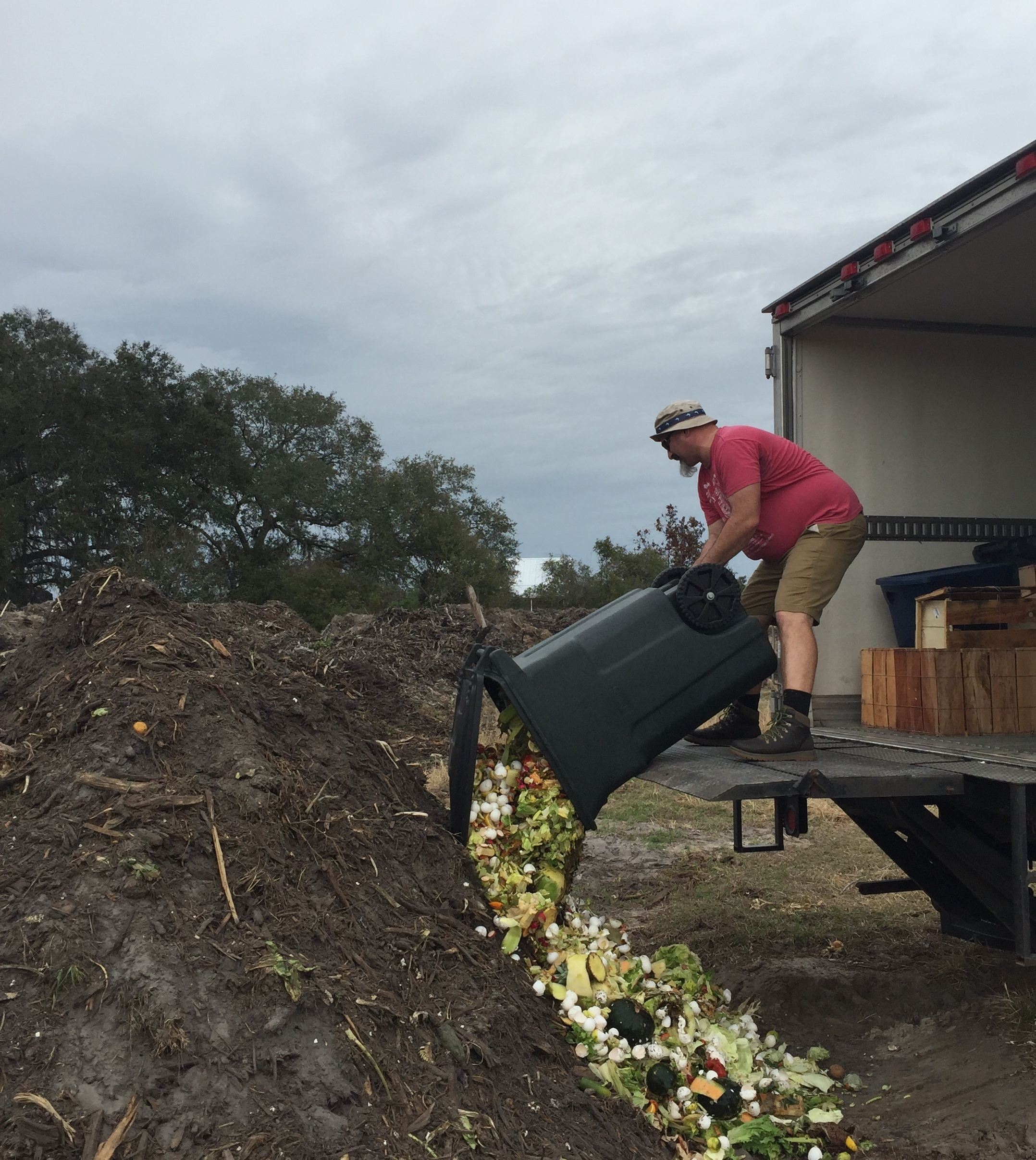 A Gamble Creek Farm team member composting leftover food from the restaurant to enrich the soil at the farm.