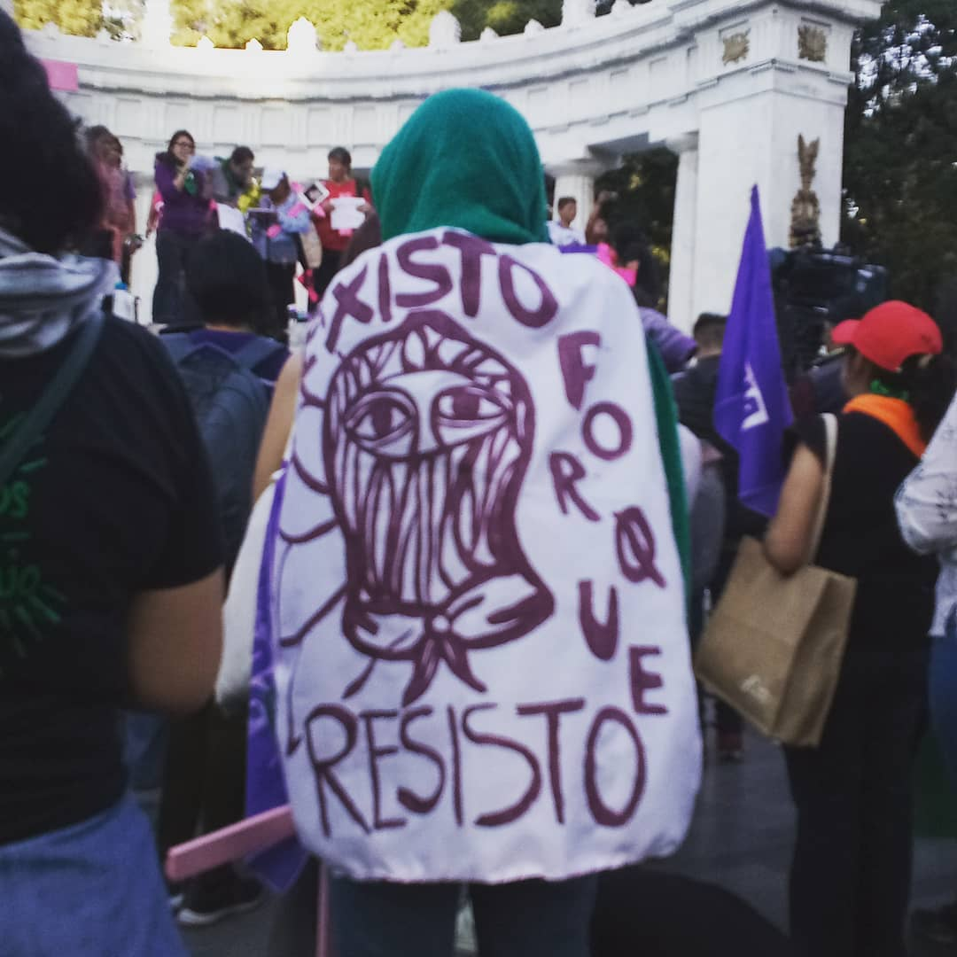"""A flag draped around a woman reads, """"I exist because I resist."""""""