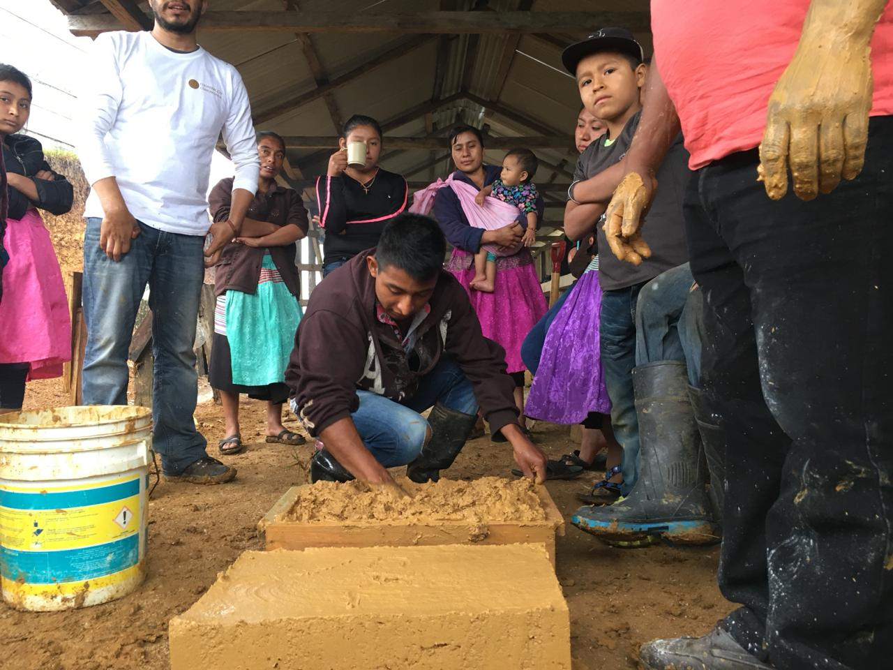 Caretakers learn to form adobe bricks on site using local materials.