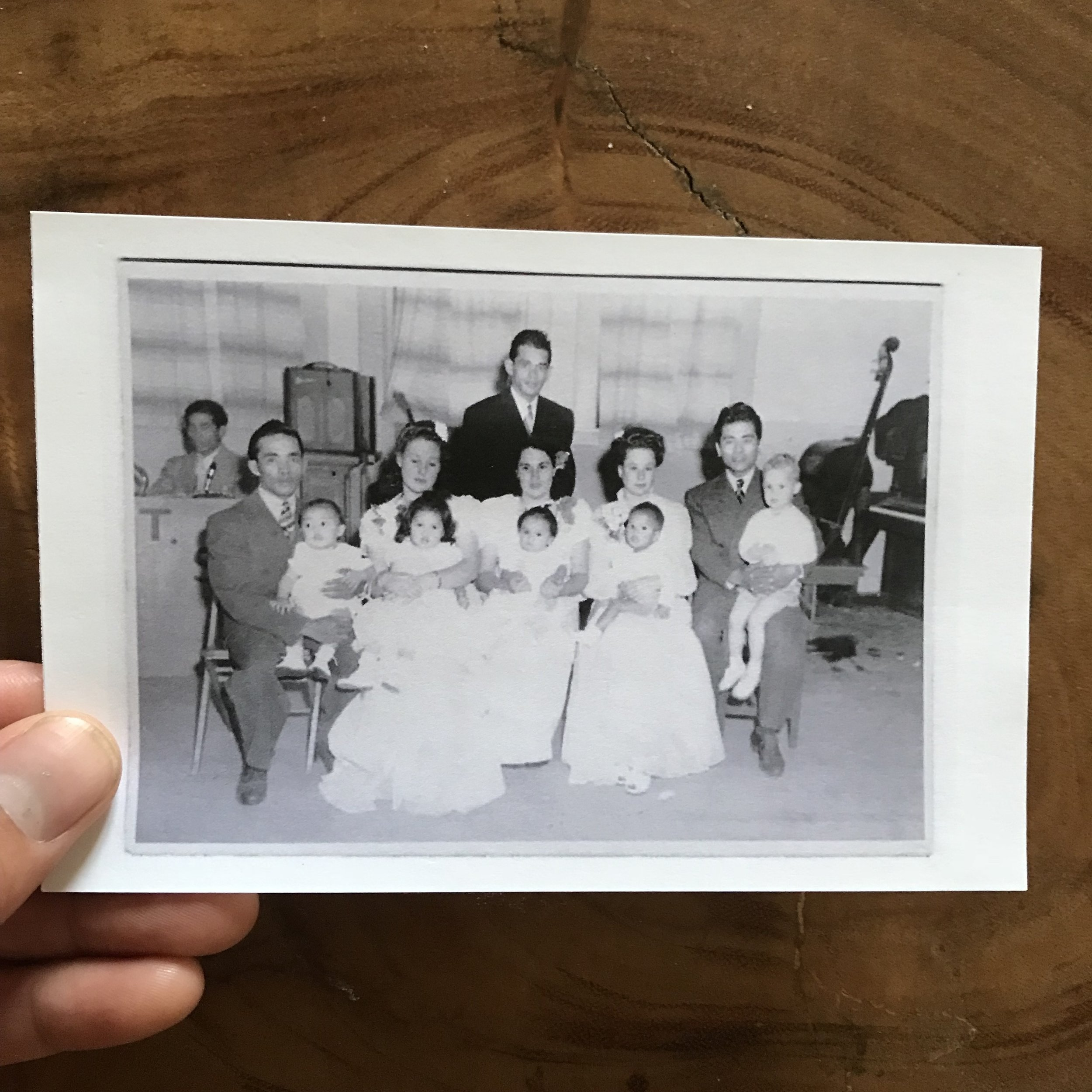 Vintage photo of Filipino annual reunion in Santa Maria, CA, circa 1950s.  Father (center) with his first wife (American,) holding my oldest sibling, Nora — who, to this day, I have never met. My uncles (left, Manong Leon and Uncle Henry, right) are to either side of my father with their American wives and mestizo children.  All this American wives talk sounds like Filipino men were stealing all the women from white men, haha. Context: during the wave of migration of Filipinos in America (1930's-1950's), only men were allowed to migrate for labor. The only option for Filipino men to find love was outside of their own race, due to Filipinas immigrating to America much later.  Take a look at how well dressed everyone is! My dad never left the house without a suit. Suave AF. I like to hark back on this time, where live music, note the double bass in the background, and dancing the cha cha was the norm. I wonder what it was like for the Asian men and masculinity within their community. I wonder what the American wives club was like at these events? I'm sure these women didn't speak Visayan (the Filipino dialect my family speaks). So many questions and not many answers, just my imagination to fill in the blanks. This oral / photo history project is a quest to mend those gaps in my disjointed historical narrative.