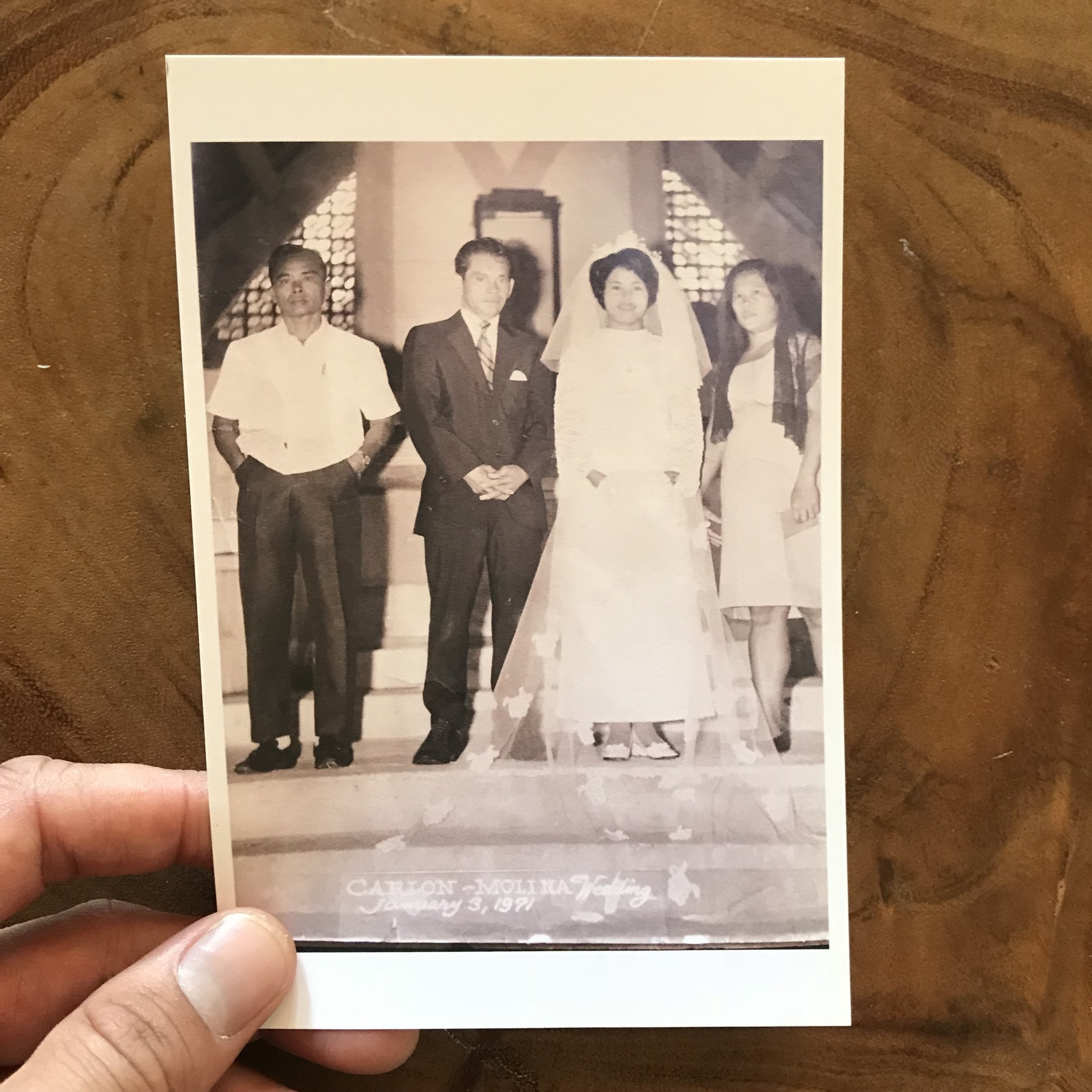 """Photo of my parents' wedding. Circa 1971 in Cabilao, Philippines.  In this photo, my dad was 60 yrs old and my mom was 20. Yep, that's a 40 yr difference. My mom was my dad's third wife... meaning he had two marriages in America and 6 kids before he decided at the very fertile age of 60 to go back to the motherland — the same small island he grew up on — to swoop up my 20 year old mother and start ANOTHER family. It's actually not too uncommon that Filipino families have an old dad and a young mom... not exactly sure why this is. Any historians, chime in.  I wish I could ask my dad, """"why?"""" A series of why's, including: why did you want more kids? I mean, I'm grateful... if he didn't think at the age of 76 when he had me to have more kids, well... I wouldn't be here posting this on Instagram rn. Your feed would be filled with other shit, like cats and food. And maybe some topless men. Well, that's what usually populates my feed..  I'm curious about my parents' relationship and how their love for each other grew, evolved, or even started for that matter. But I understand they loved each other... and I have many, many, many questions... but I'll just stop, for now, at their unconditional love for me and my family."""