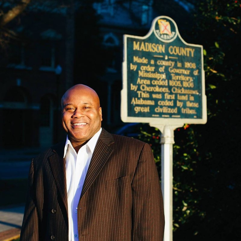"""William H. Hampton is a native of Huntsville-Madison County, Alabama. Educated in the Huntsville City School System during the 1960s and 70s, William was one of the first African-American students to attend Farley School, and Weatherly Elementary School. Hampton is active in preserving African American history in Huntsville-Madison County. He is one of the organizers of """"Festival of Voices"""", a cemetery stroll at Huntsville's historic Glenwood Cemetery where he portrays historic figures there, and at Maple Hill Cemetery. He founded Huntsville Revisited Tours, providing guided tours in the community, and he shares his photographs and stories documenting local history on his social media sites; Huntsville Revisited (one of the most popular community pages in the United States), Alabama Revisited, and Negro History of Huntsville-Madison County, Alabama. Hampton has received national and local recognition for his historic preservation work in Huntsville-Madison County. In 2016 he received the National Community Service Award from the Twickenham Chapter of the Daughters of the American Revolution; the Community Hero Award from Oakwood University in 2018, and was a 2018 Black History Honoree at Madison Mission Seventh-day Adventist Church. Along with serving as chair of this committee, Hampton is a member of the local William Hooper Councill Alumni Association and the Huntsville Historic Society Marker Committee, and a board member of the Scottsboro Boys Museum and Cultural Center and the Huntsville Pilgrimage Association. Professionally, Hampton serves as Food and Nutrition Supervisor at Huntsville Hospital, a volunteer instructor for LearningQuest, and a consultant for Earthscope Environmental Education Department – Huntsville City Schools.  -"""