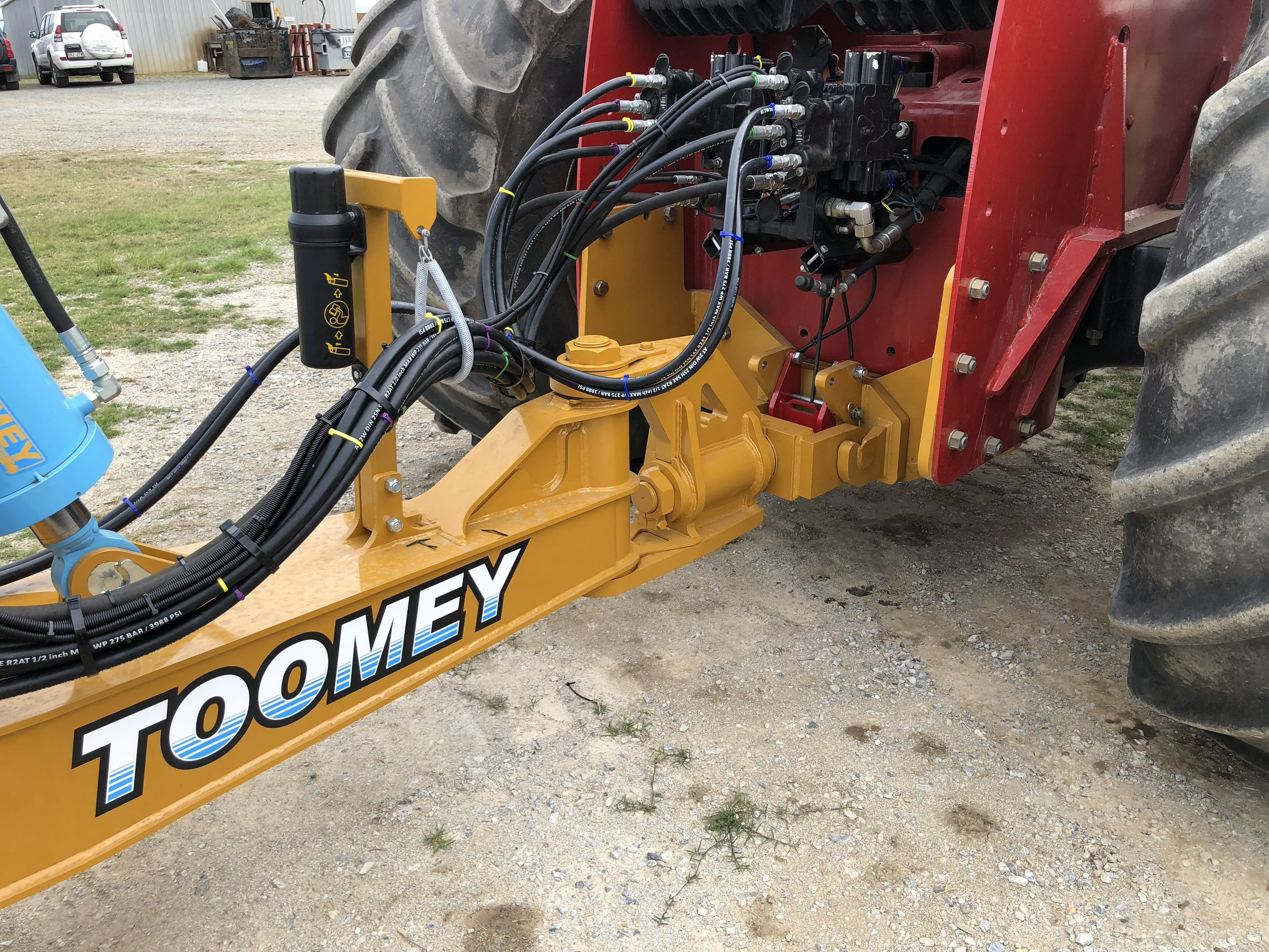 "Swivel Hitch - The Toomey Scrapers are connected to the tractors with a 360 degree rotation Swivel Hitch.This hitch is connected to a quick-disconnect coupling fabricated to the end of a custom made towbar. This coupling is positioned as close to the back axle as possible to reduce the weight transfer to this axle.The closer the coupling is to the back axle, the less weight is taken away from the front axle. The further towards the scraper the connecting point is, the more leverage is applied to the back axle, transferring weight from the front axle to the back axle – the ""fat kid on a see-saw"" scenario!"