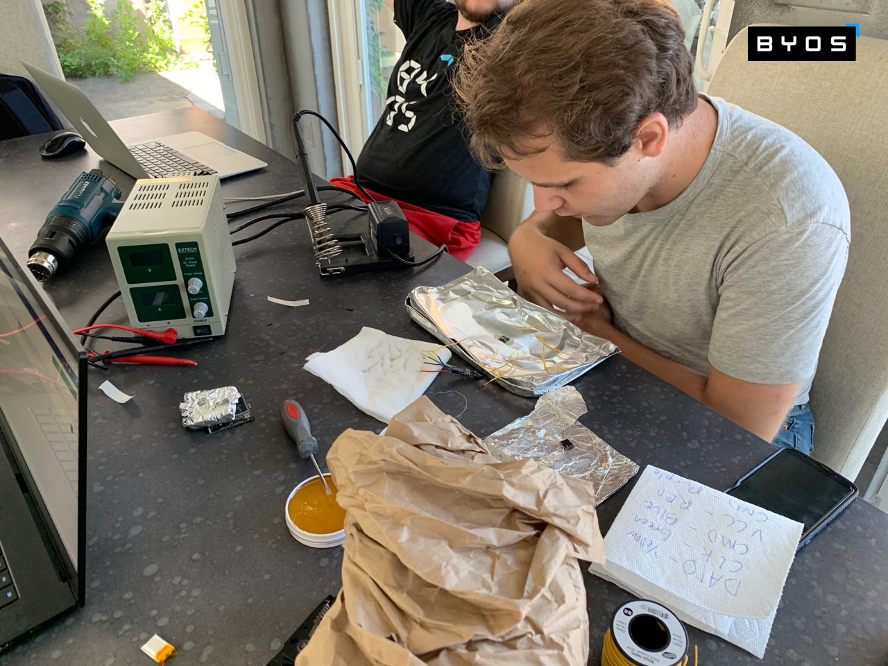Max unsoldered the eMMC from the Byos Portable Secure Gateway Hardware board, to try to access its raw information. He is seen here carefully soldering wires directly to the FBGA.