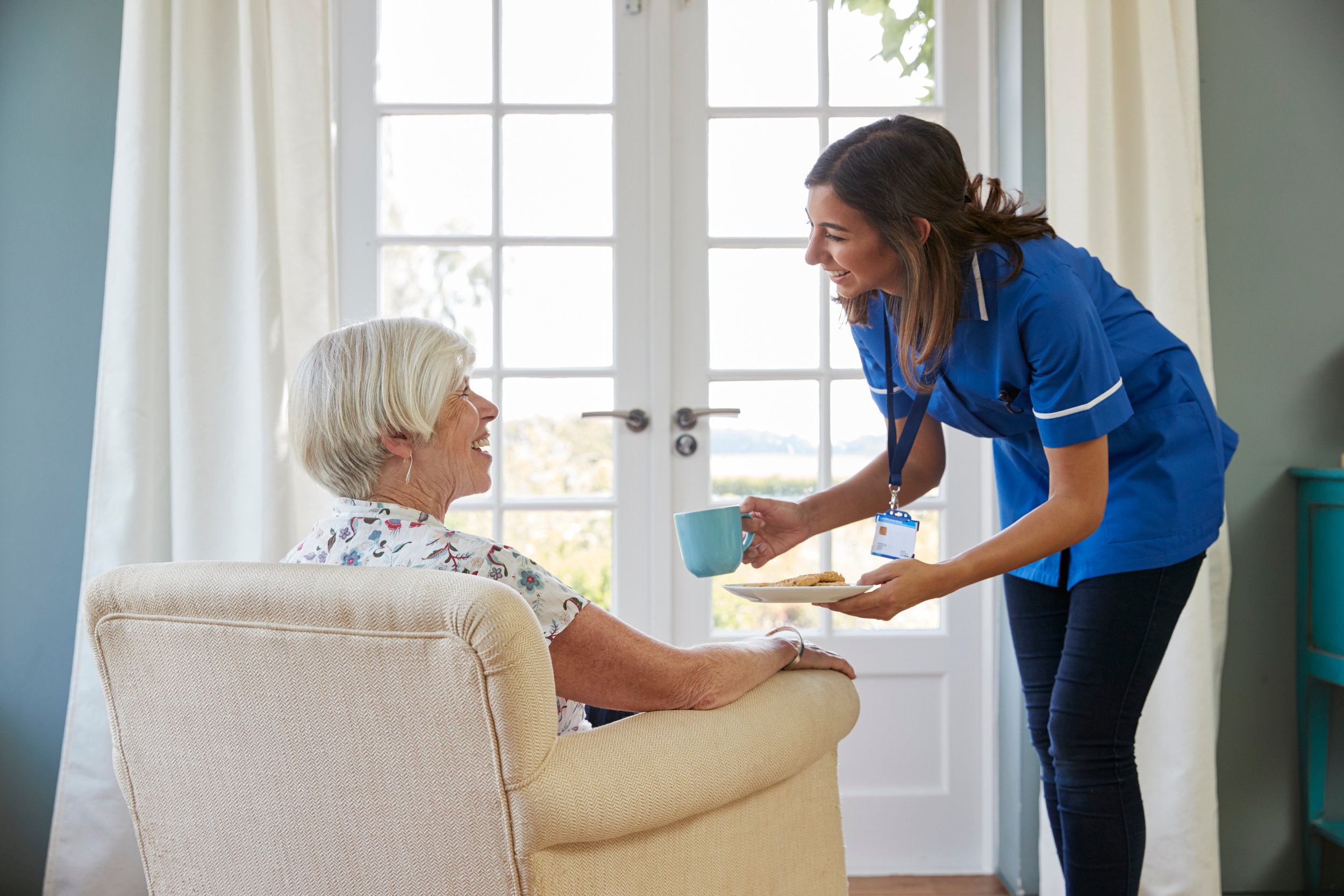 Canva - Nurse Serving Tea and Biscuits to Senior Woman at Home.jpg