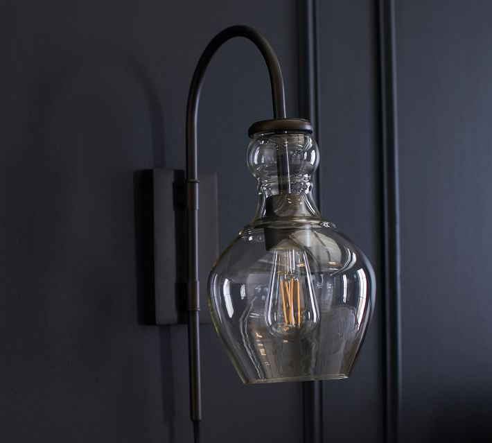The Flynn Recycled Glass Sconce elegantly accentuates the richness of the navy paneled wall.