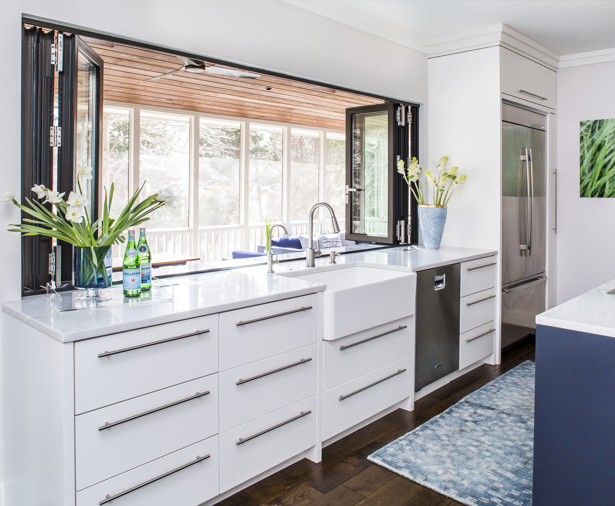 Contemporary kitchen with white cabinetry, apron sink, stainless steel appliances and accordion windows