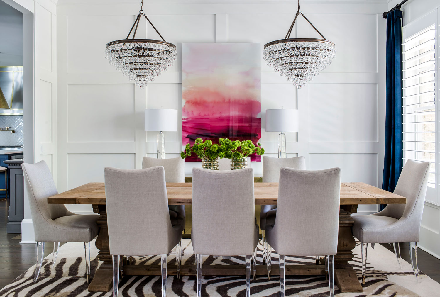 Contemporary elegant dining room with lucite dining chairs and rustic dining table