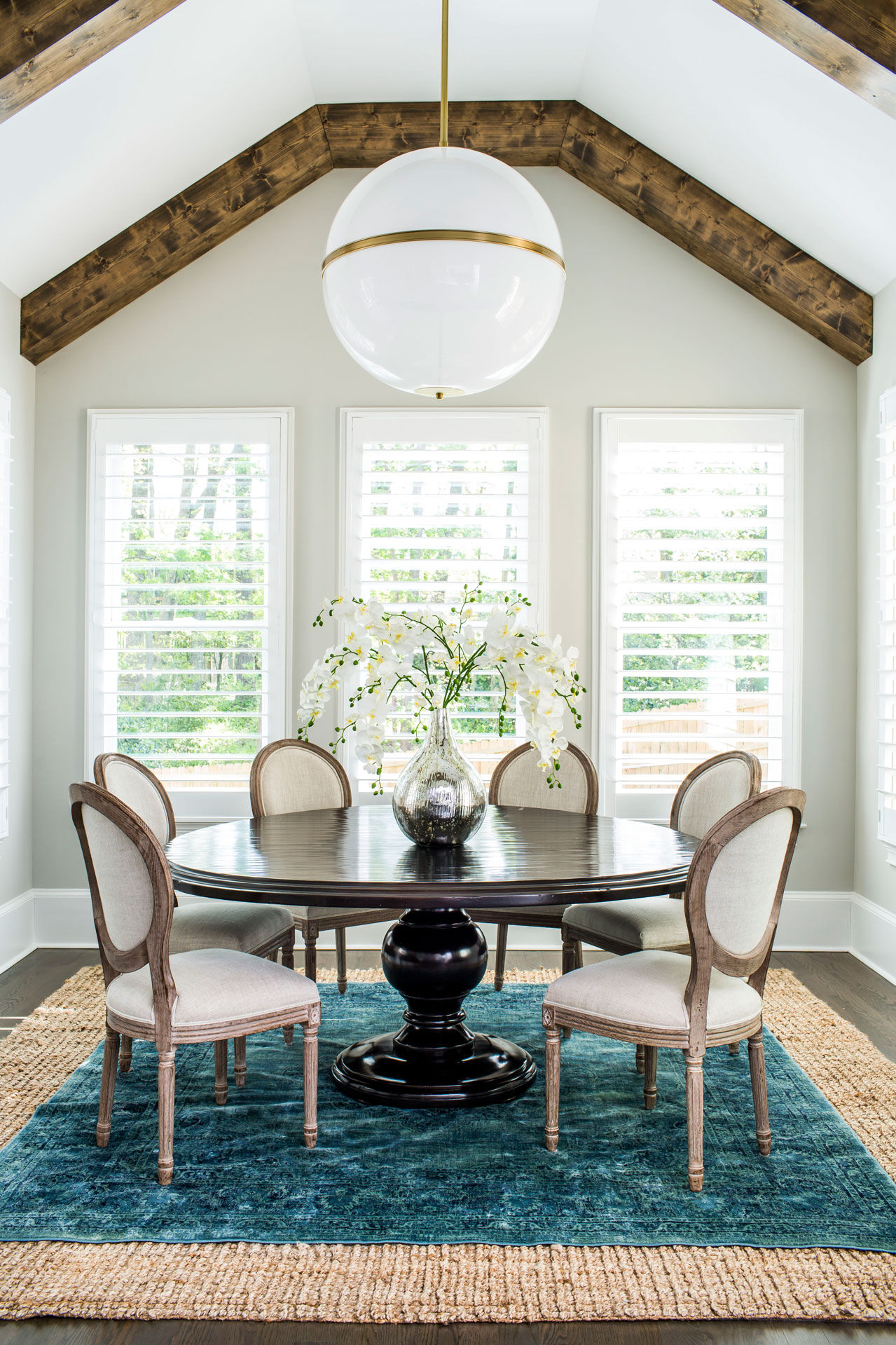 Contemporary breakfast room with layered teal and jute rugs