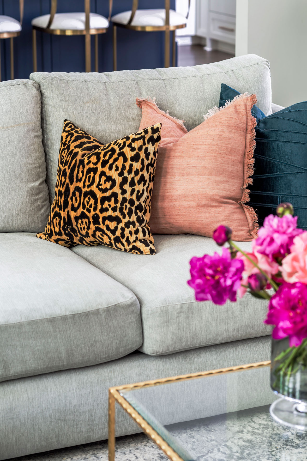 Grey velvet sectional with colorful printed throw pillows