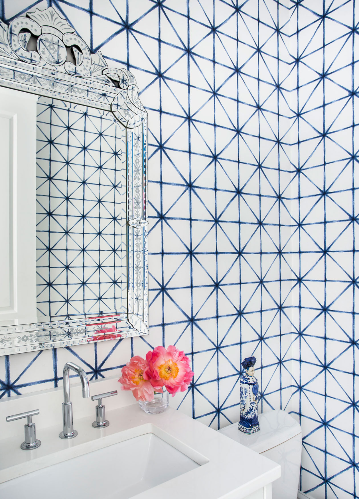 Blue and white geometric wallpaper in powder room
