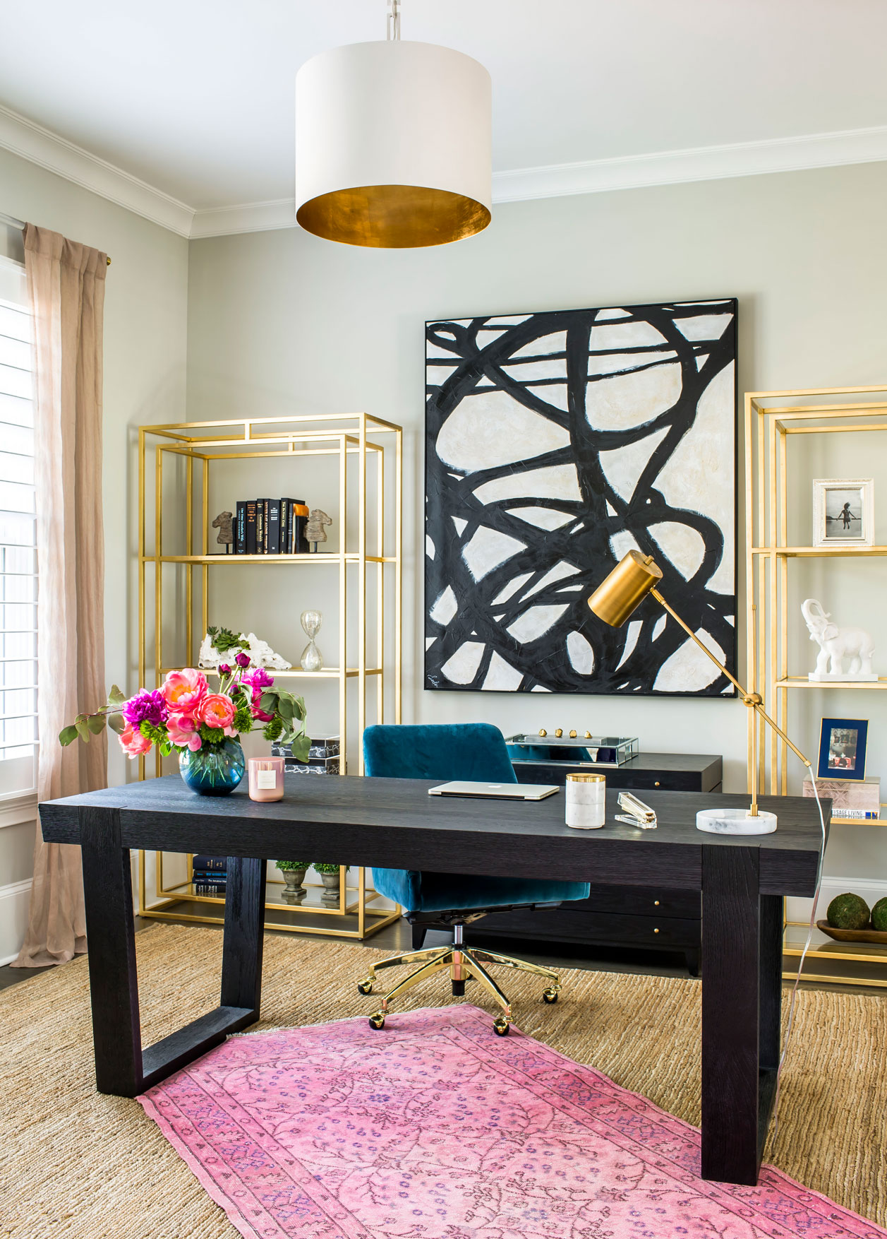 Colorful home office with freestanding desk, abstract art, pink rug and brass shelves