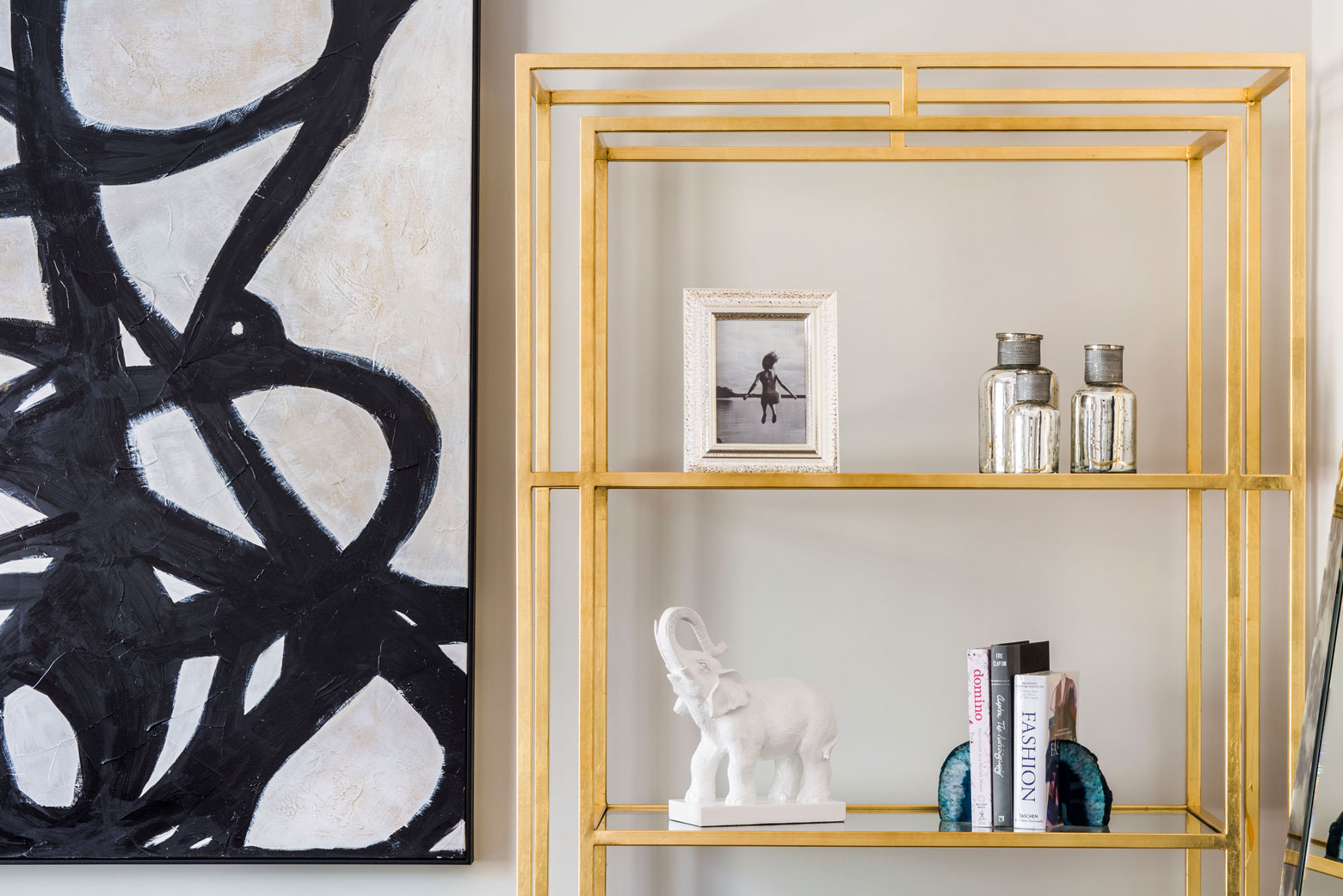 Brass shelving with books, crystal geode bookends, picture frames, and decorative glass jars