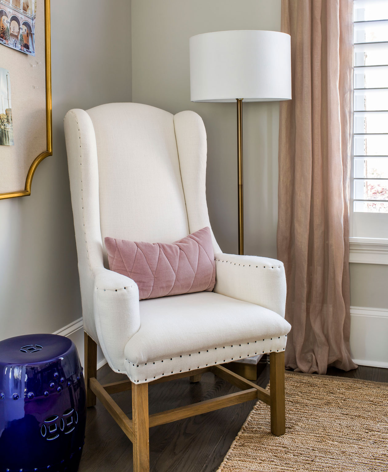 Ivory upholstered chair with wooden legs and blue side table in corner of home office