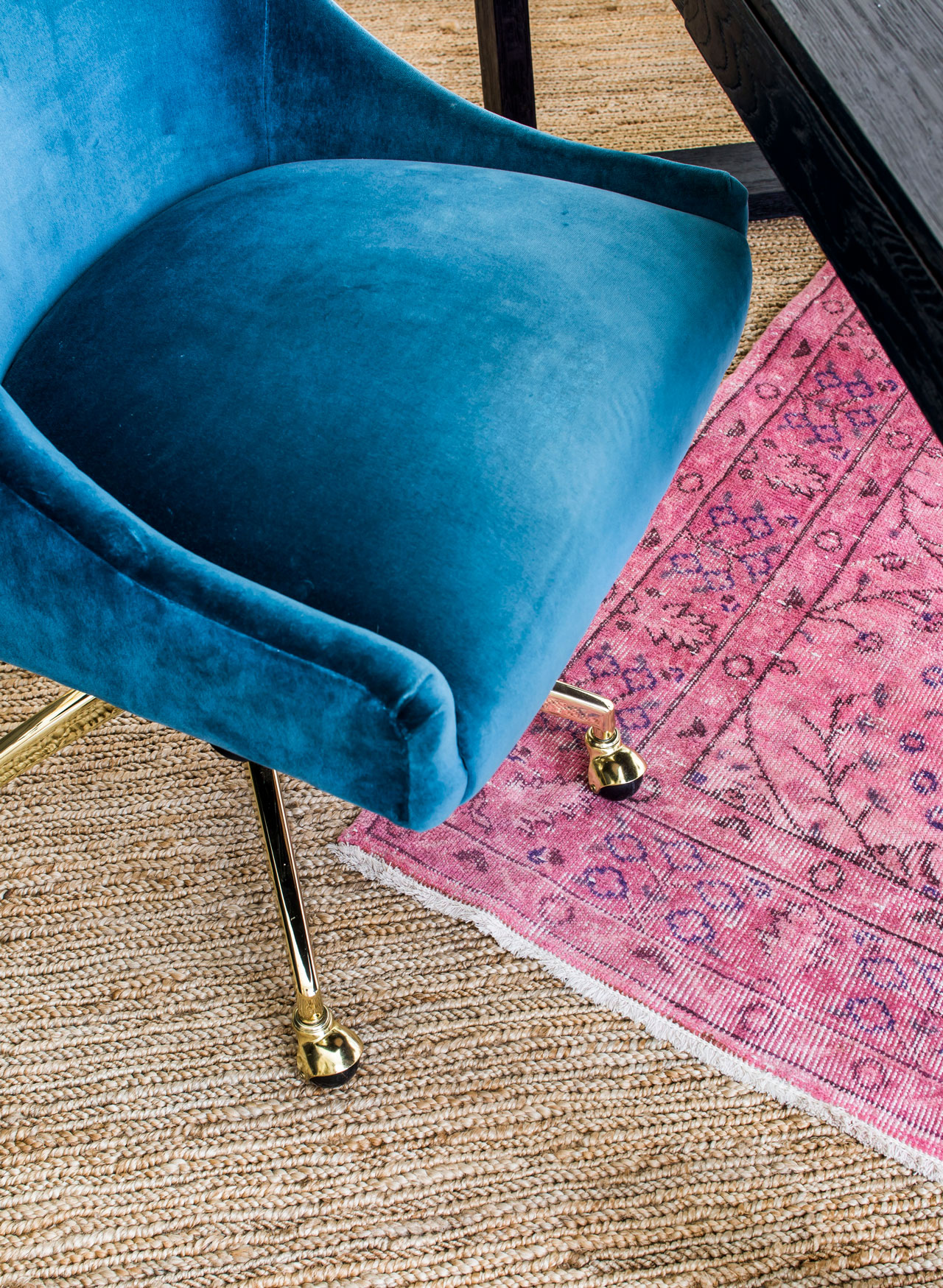 Velvet upholstered desk chair on layered jute and pink area rugs in home office