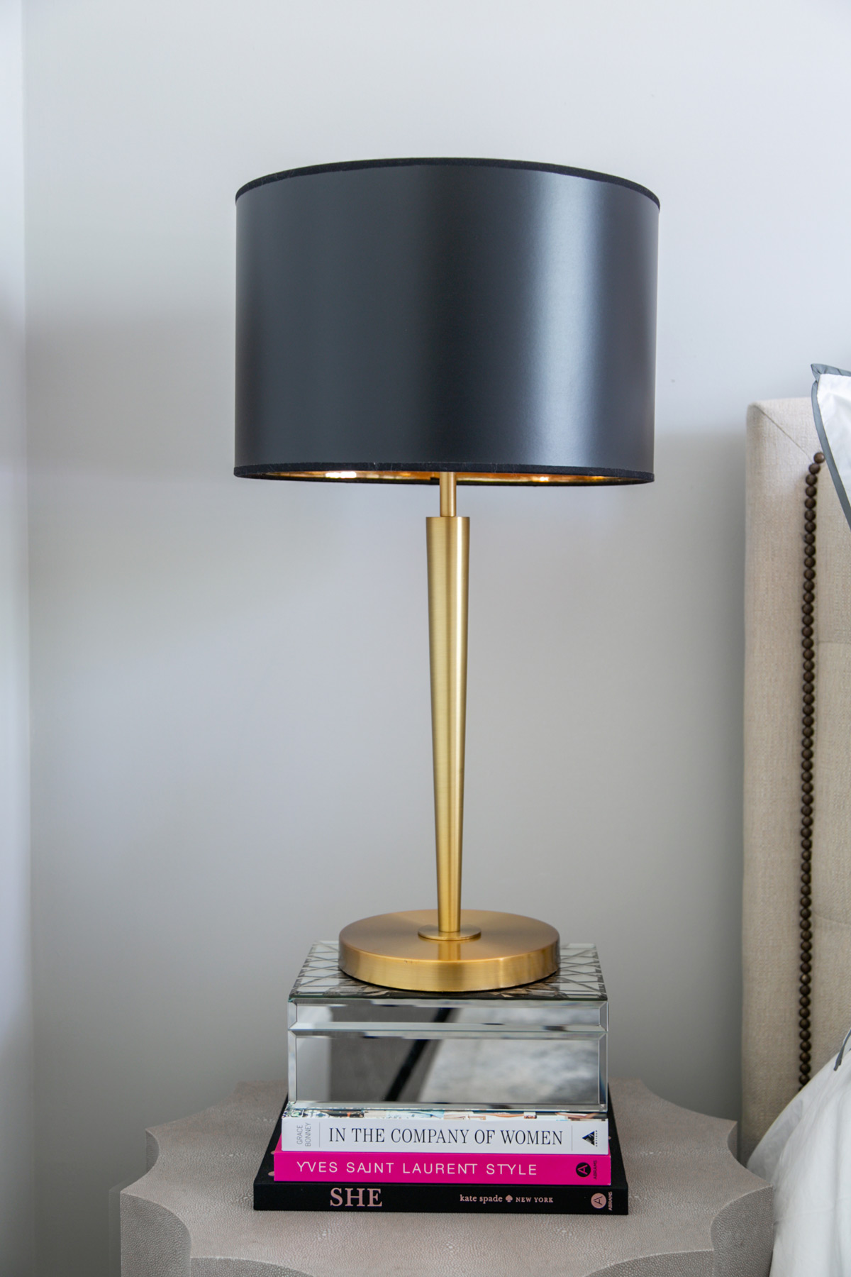 Concrete bedside table with black and brass table lamp sitting on a stack of books
