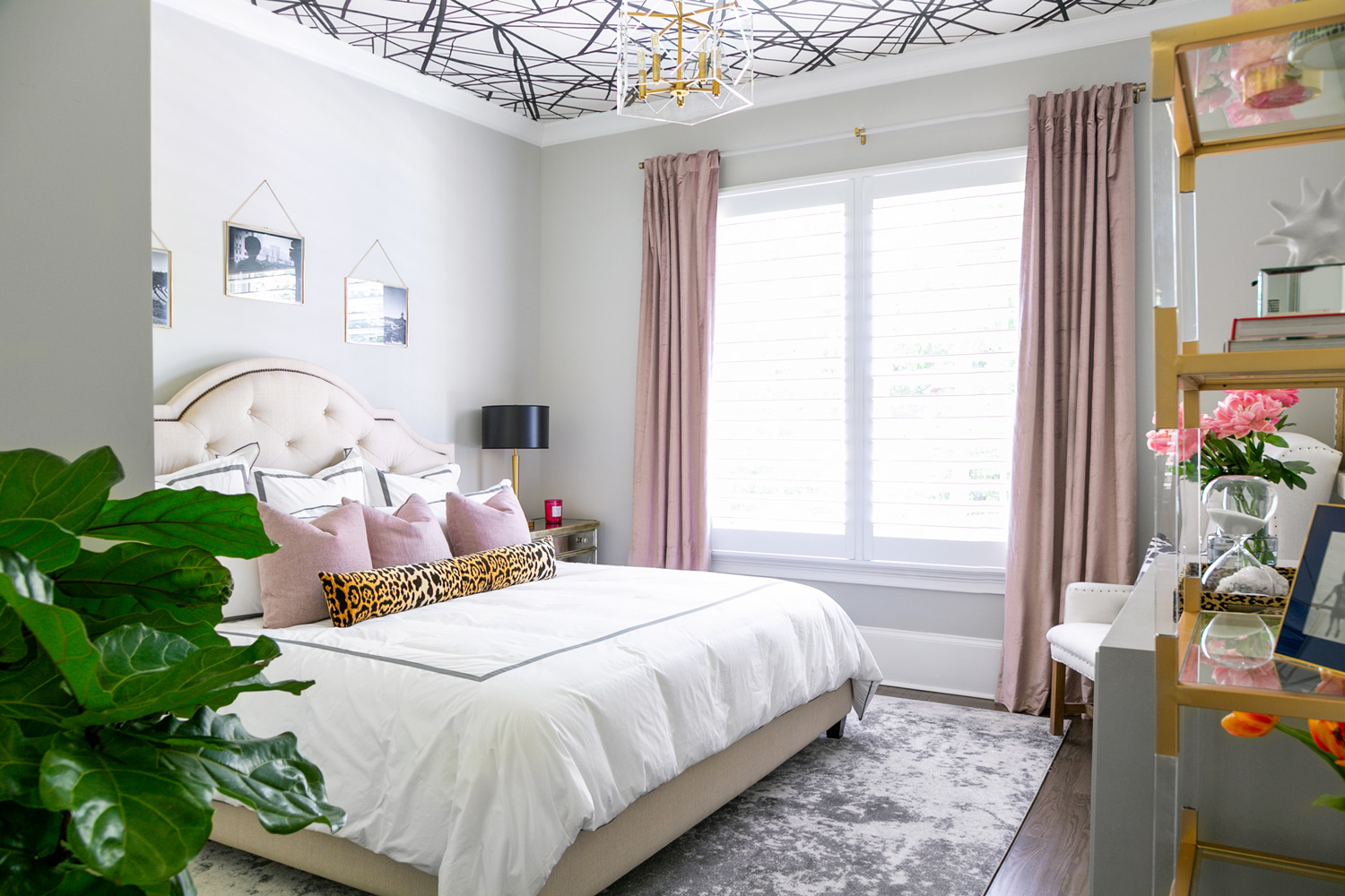 Guest bedroom with abstract wallpapered ceiling, brass lighting, and pink velvet decor