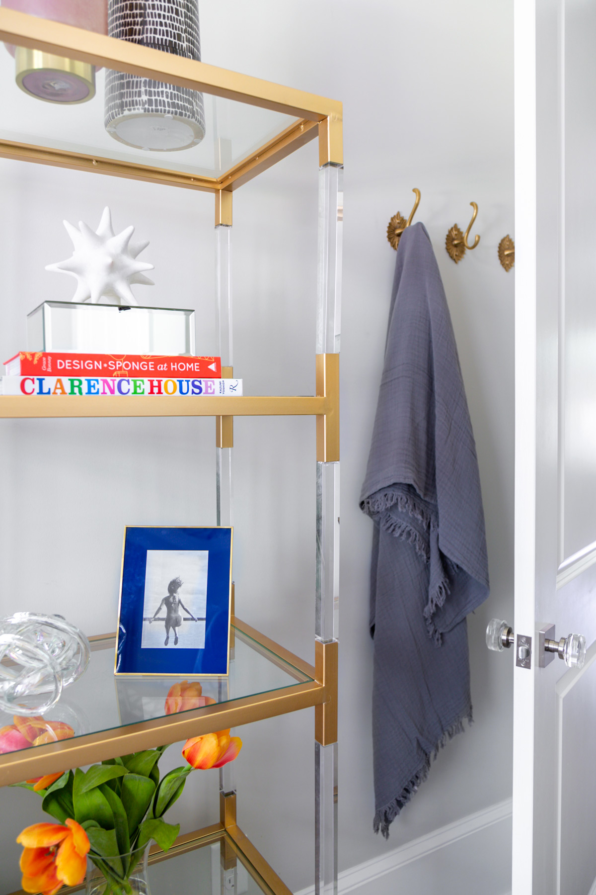 Glass shelves in guest bedroom with colorful books and accessories