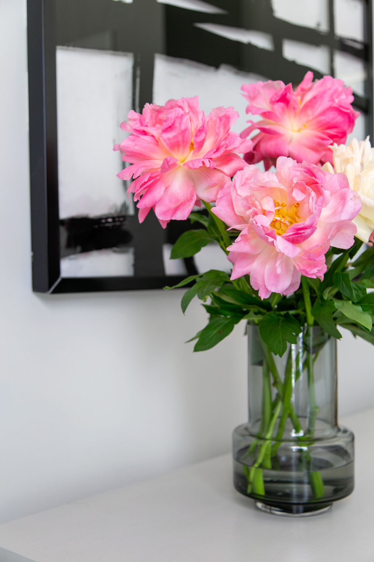 Glass vase of peonies on dresser in front of black and white abstract art