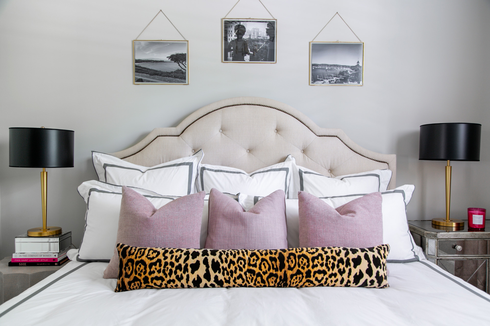 Chic guest bedroom with black and brass lamps, upholstered headboard, brass accessories, and textured throw pillows