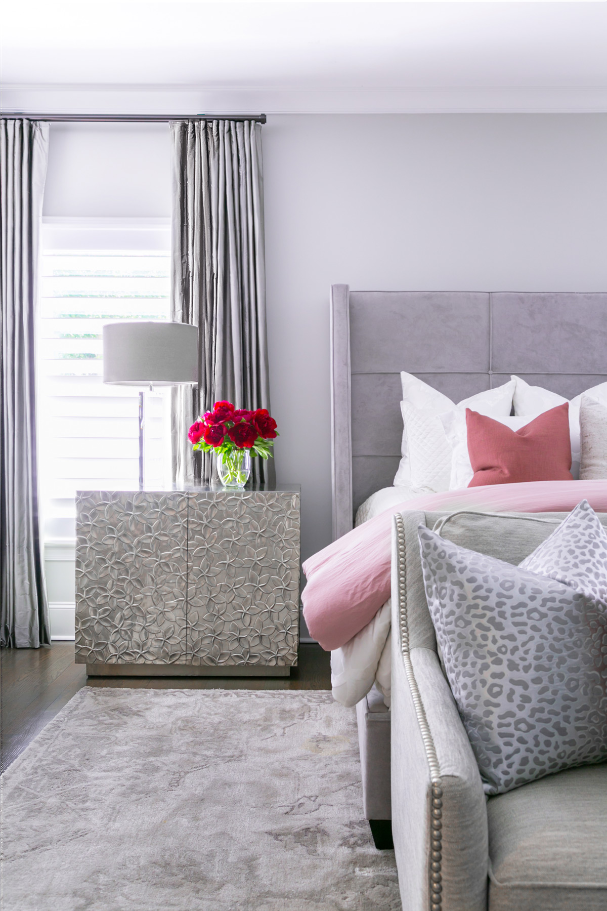 Chic contemporary master bedroom with silver floral embossed nightstands and pink bedding
