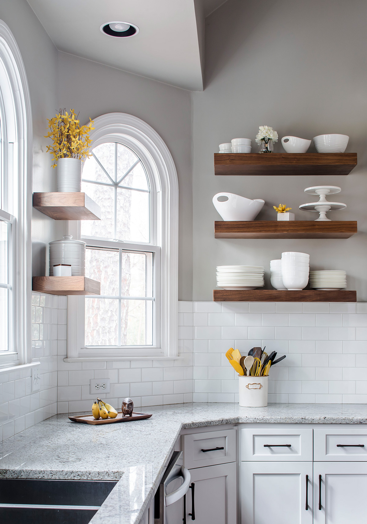 Transitional grey and yellow kitchen with floating wood shelves