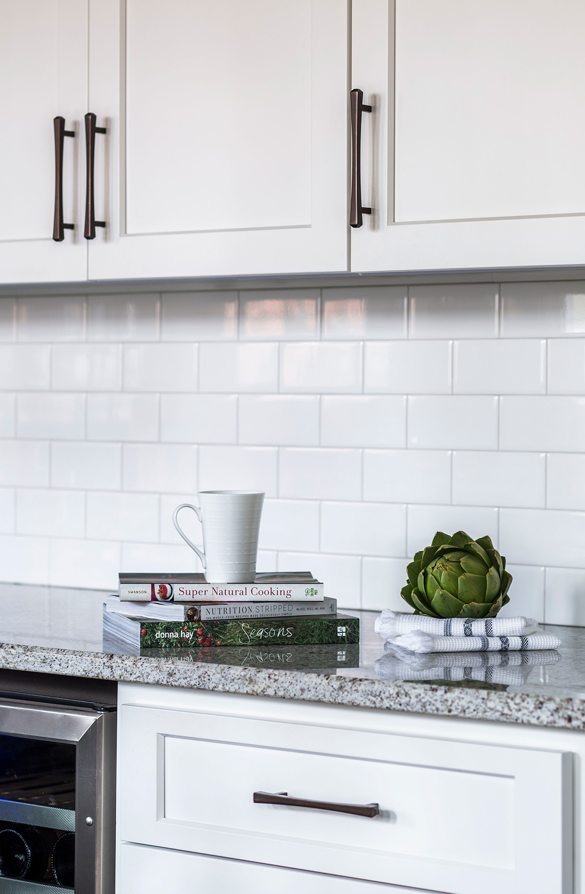 Cookbooks sit on grey granite countertops in kitchen